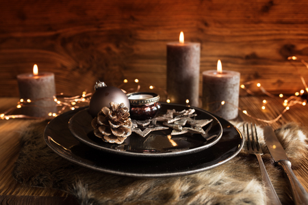 Festive christmas table setting with candles in country house style for a dinner Imagens