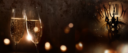 Champagne for the new year on dark background with a clock and festive golden and silver bokeh