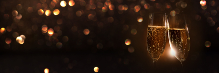 Champagne glasses in the night of new year with a festive golden bokeh for a background