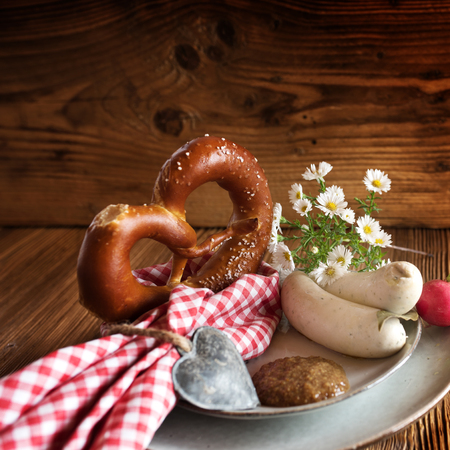 Bavarian still life with white sausage and salt pretzel on rustic wooden table for a oktoberfest background