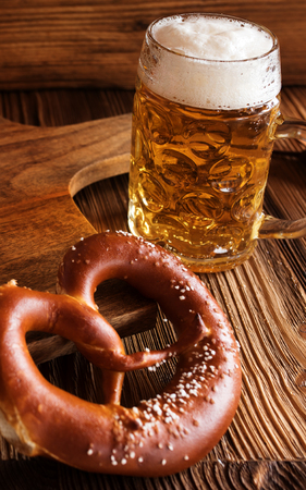 Bavarian bright draft beer with salt pretzel on rustic wooden table