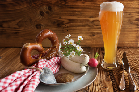 Fresh oktoberfest wheat beer with salt pretzel and white sausage on rustic wood