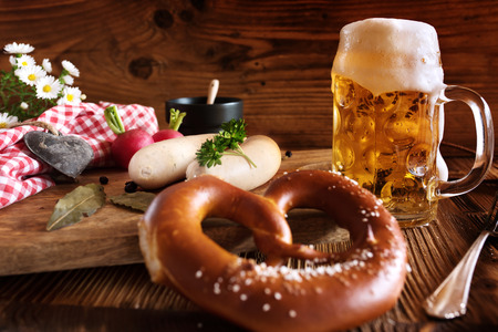 Fresh oktoberfest beer with salt pretzel and white sausage on rustic wood Imagens