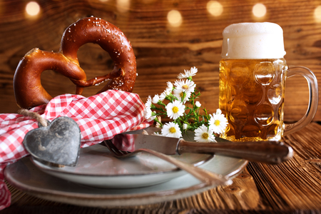 Oktoberfest place setting traditional with beer and salt pretzel on rustic wood Imagens
