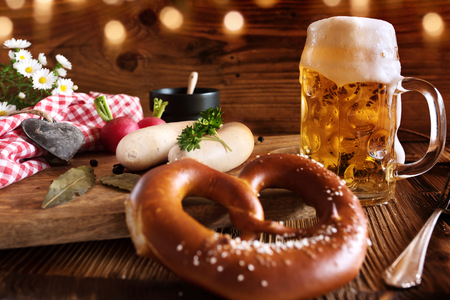 Oktoberfest traditional with beer pretzel and white sausage on rustic wood