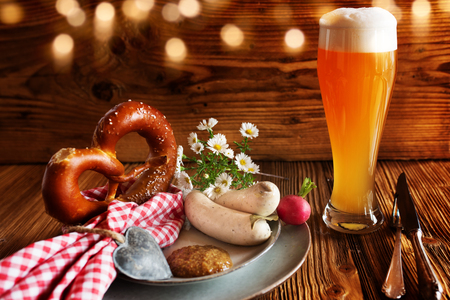 Oktoberfest traditional with wheat beer pretzel and white sausage on rustic wood Imagens