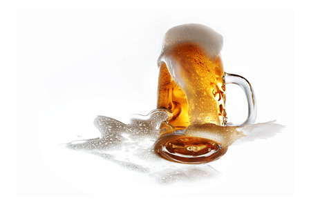 Glass of fresh draft beer with overflowing foam isolated