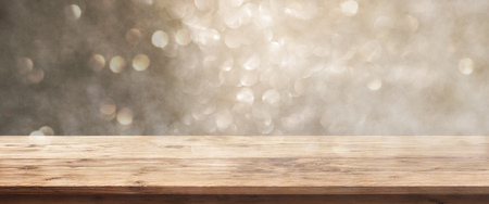 Golden bokeh background with rustic wooden table for a christmas decoration Фото со стока