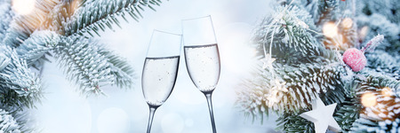 Decorated fir branches in winter with champagne glasses and golden bokeh for christmas Stock Photo