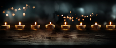 Burning candles on dark blue background with golden lights