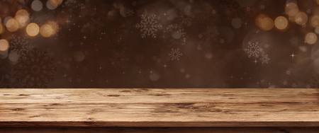 Empty rustic wooden table in front of christmas background with festive golden bokeh and snowflakes for decorations