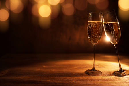 Background with golden bokeh and tingling champagne for christmas and new year congratulations