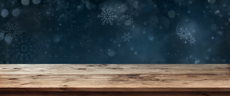 Rustic wooden table in front of dark blue winter background with snowflakes and stars for a christmas decoration