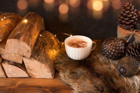 Cozy christmas still life with a cup hot cappuccino and golden bokeh