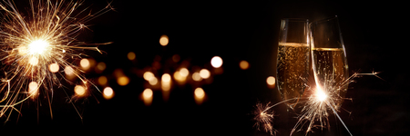 Champán para la víspera de año nuevo con bokeh dorado y bengalas para celebrar