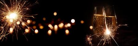 Szampan na sylwestra ze złotym bokehem i zimnymi ognie do świętowania