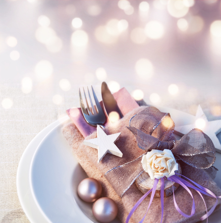 Festive christmas place setting with tender pink background and golden bokeh