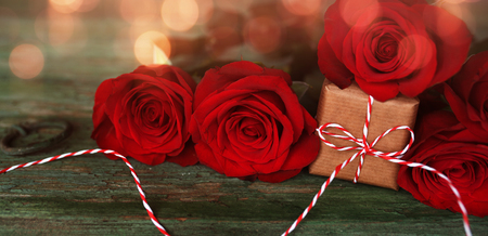 Red roses with a small gift decorated on old rustic wood and bright bokeh for valentine's day