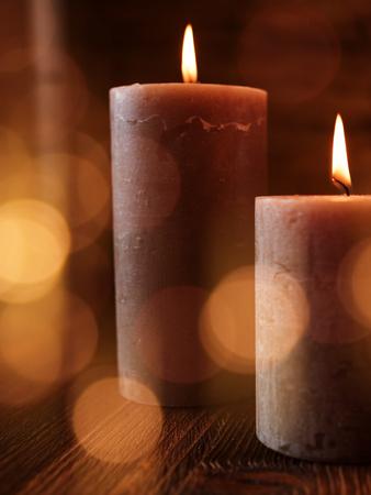 Zwei brennende Kerzen mit festlichen goldenen Lichteffekten auf dunklem Holz für besondere Momente
