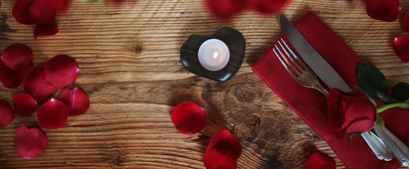 Place setting in red wooden table for a romantic valentines dinner