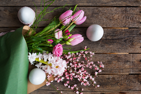 Tender easter eggs and colorful spring bouquet on old rustic wooden background