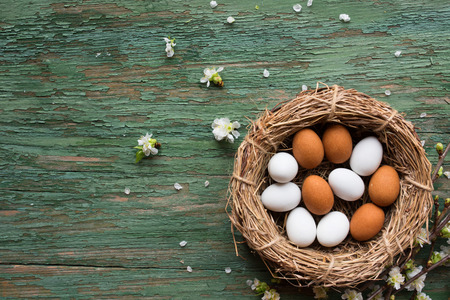 Eggs in a basket and cherry blossoms on green old shabby wood for a easter background