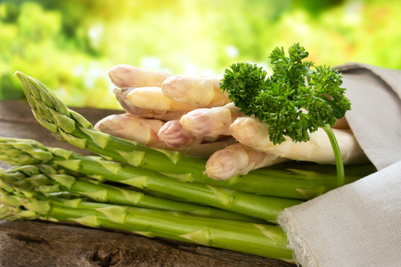 Fresh asparagus on rustic wood in sunny springtime Banco de Imagens