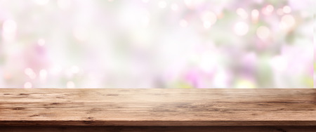 Abstract tender pink bokeh background with a wooden table for a mothers day decoration