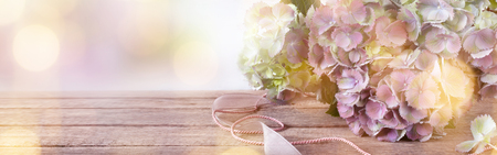 Tender pink blossoms on vintage wood with golden bokeh for a wedding