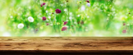Rustic wooden table with blurred colorful flower meadow background for a decoration