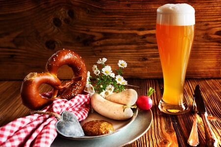 Bavarian specialties fresh beer with salt pretzel and white sausage on rustic wood for the Oktoberfest