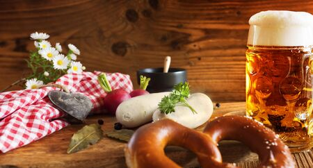 Fresh bavarian beer with salt pretzel and white sausage on rustic wood for the Oktoberfest