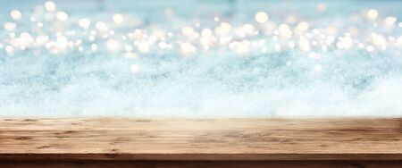 Abstract winter panorama with wooden table and bright bokeh for a christmas decoration