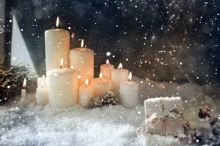 Christmas decoration with burning candles in a snowy winter night