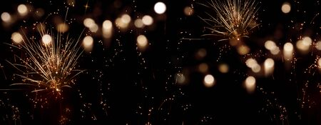 Golden firework in the dark night sky with festive bokeh for new year greetings