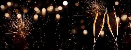 New Year champagne with fireworks on night sky with golden bokeh
