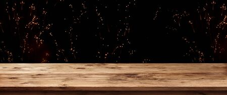 Old rustic wooden table in front of firework on night sky for a background decoration Banco de Imagens