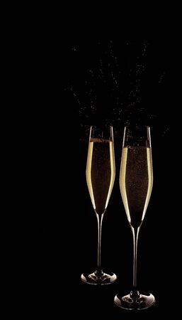 Two modern glasses with golden champagne isolated on black background Stock Photo