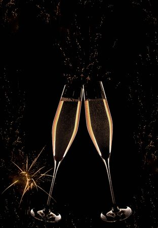 Golden champagne with fireworks on night sky for a vertical new year background Stock Photo