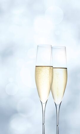Two modern champagne flutes on bright blue bokeh background