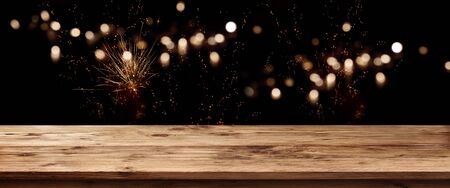 Holiday background with wooden counter and golden firework on night sky