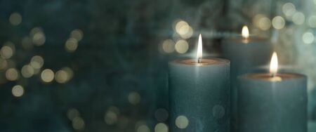 Candels and festive golden bokeh on dark background Stock Photo