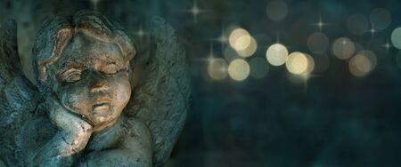 Angel sculpture with golden bokeh on dark background 写真素材