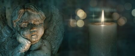 Angel sculpture with candles and golden bokeh on dark background