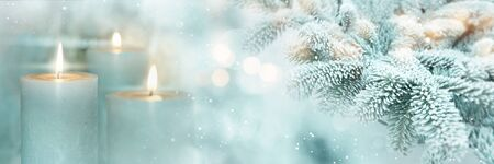 Winter scene background for christmas with burning candles and fir branches