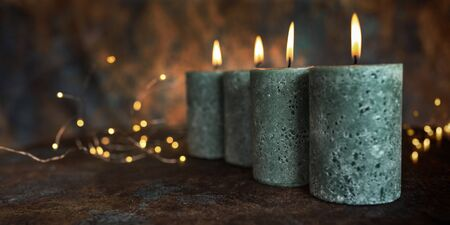 Four candles on patinated background for christmas
