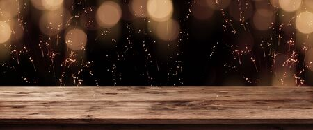 Festive golden bokeh on dark night sky with empty wooden table for a christmas decoration