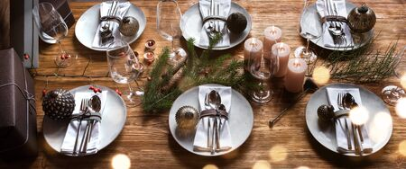 Modern table decoration on a wooden table for christmas with golden bokeh for a family dinner
