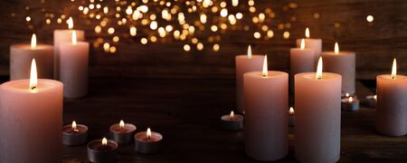 Burning candles in darkness with light effects