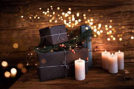 Christmas presents festively decorated on old wooden background with golden lights